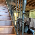 Dulux Dark Bronze wrought iron railing on polished timber staircase with knuckles/knobs, heavy end post and curved end scroll